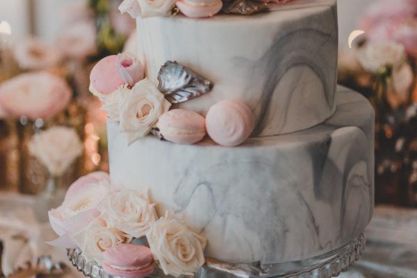 Dwupiętrowy tort z motywem marmuru, przyozdobiony pudrowymi różyczkami i makaronami