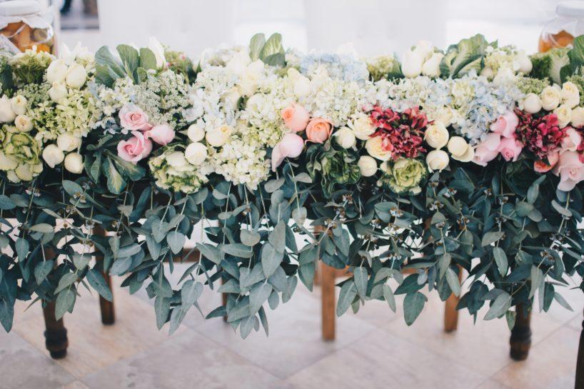 Bogata zielono pastelowa kompozycja kwiatowa zajmująca cały prostokątny stół