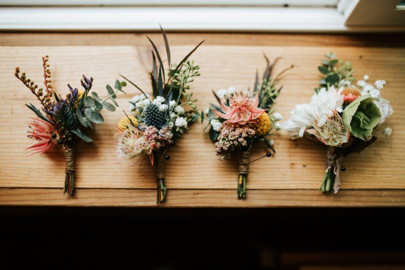 Cztery kompozycje w postaci butonierek z polnych kwiatów ułożone w jednym rzędzie na drewnianym parapecie