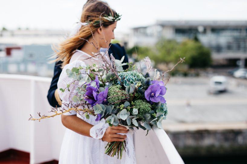 Para Młoda na dachu jakiegoś budynku, Panna Młoda patrząca przed siebie i trzymająca na pierwszym planie zielono-fioletową dużą kompozycję ślubną