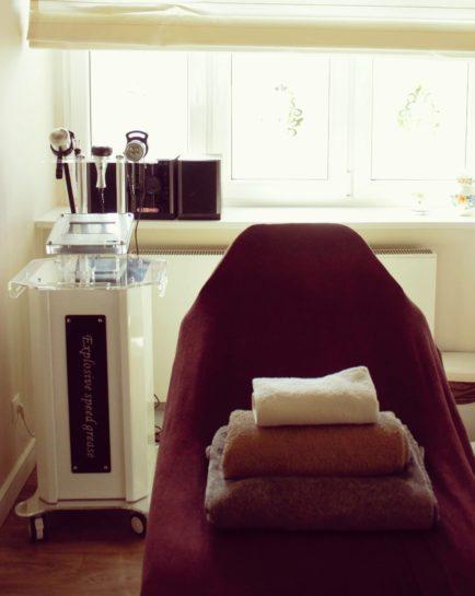 Gabinet kosmetyczny, fotel kosmetyczny, a po lewej stronie specjalistyczna aparatura do zabiegów kosmetycznych