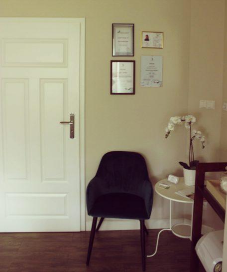 Gabinet kosmetyczny, mały stolik i butelkowo- zielony fotel, certyfikaty na ścianie