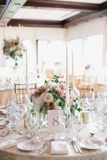 Dekoracje ślubne na okrągłym stole, z wysokimi, białymi świecami i niskim pastelowym bukietem.