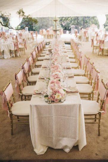 Dekoracje ślubne w pastelowych kolorach na prostokątnym stole, w namiocie weselnym