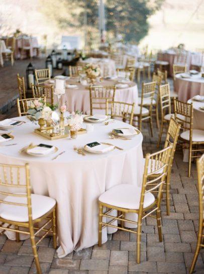 Okrągły stół weselny z dekoracjami w pudrowym różu i krzesłami chiavari