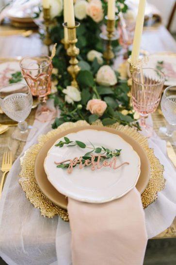 Dekoracja stołu weselnego, ze złotym podtalerzem, jasnymi kieliszkami i winietką ułożoną na białym talerzu, przystrojona wiązanką kwiatów.