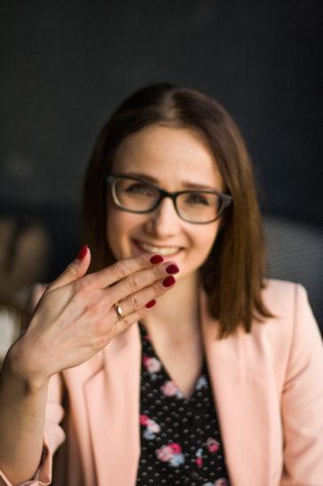 Uśmiechnięta konsultantka pokazująca na swojej dłoni złotą obrączkę