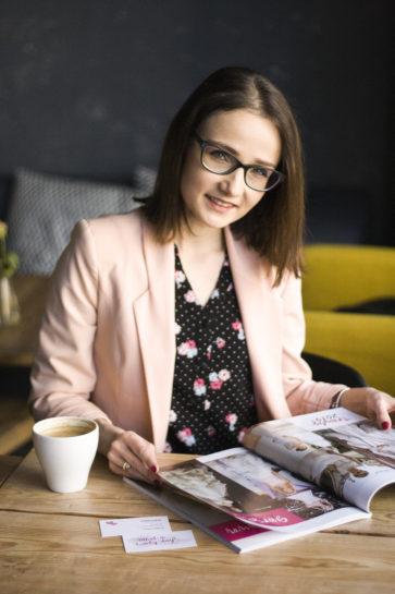 Konsultantka ślubna przeglądająca gazetę ślubną przy filiżance kawy