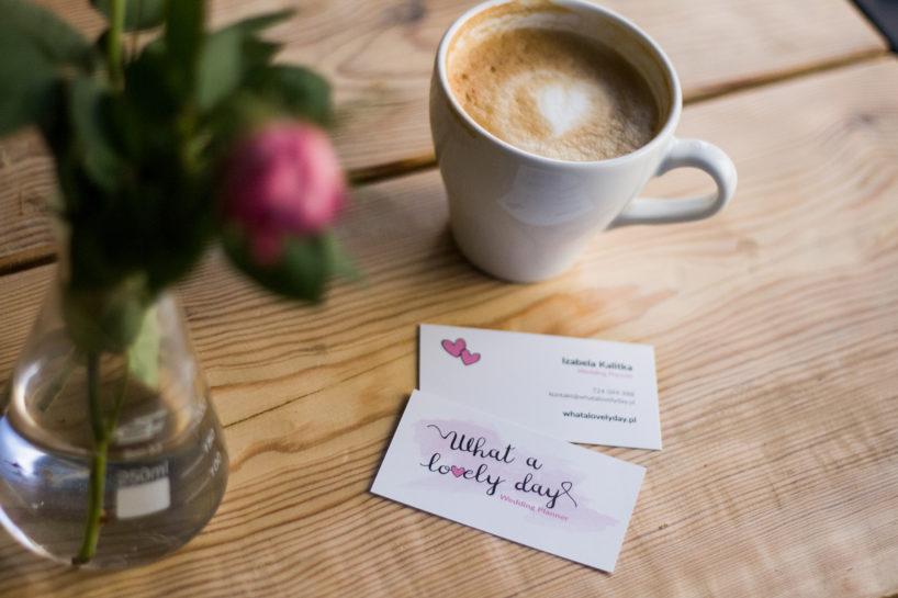 Kazdr na wizytówkę firmy What a lovely day, w tle filiżanka kawy i bukiet kwiatów w wazownie ze zlewki