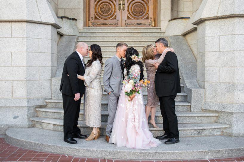 Trzy całujące się przed wejściem do kościoła pary: para młoda i i ich rodzice