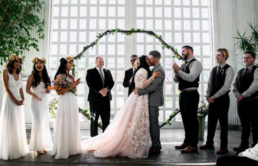 Ceremonia zaślubin, para młoda składa sobie pocałunek, a z uśmiechem przypatrują się jej druhny i drużbowie, którzy klaszczą i wiwatują