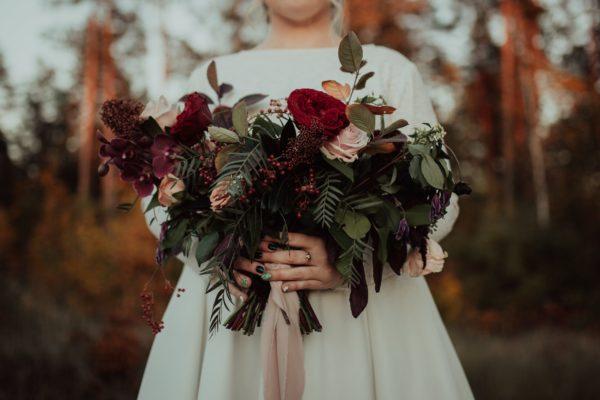Duży bukiet ślubny w kolorach jesieni z jedwabną wstążką, trzymany przez Pannę Młodą w białej sukni
