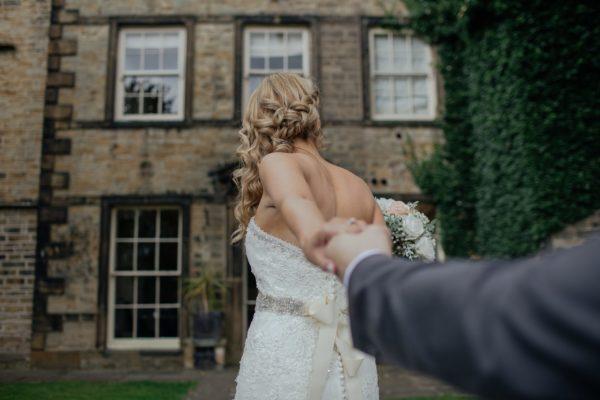 Ujęcie na tył fryzury ślubnej Panny Młodej trzymanej za rękę przez swojego wybranka