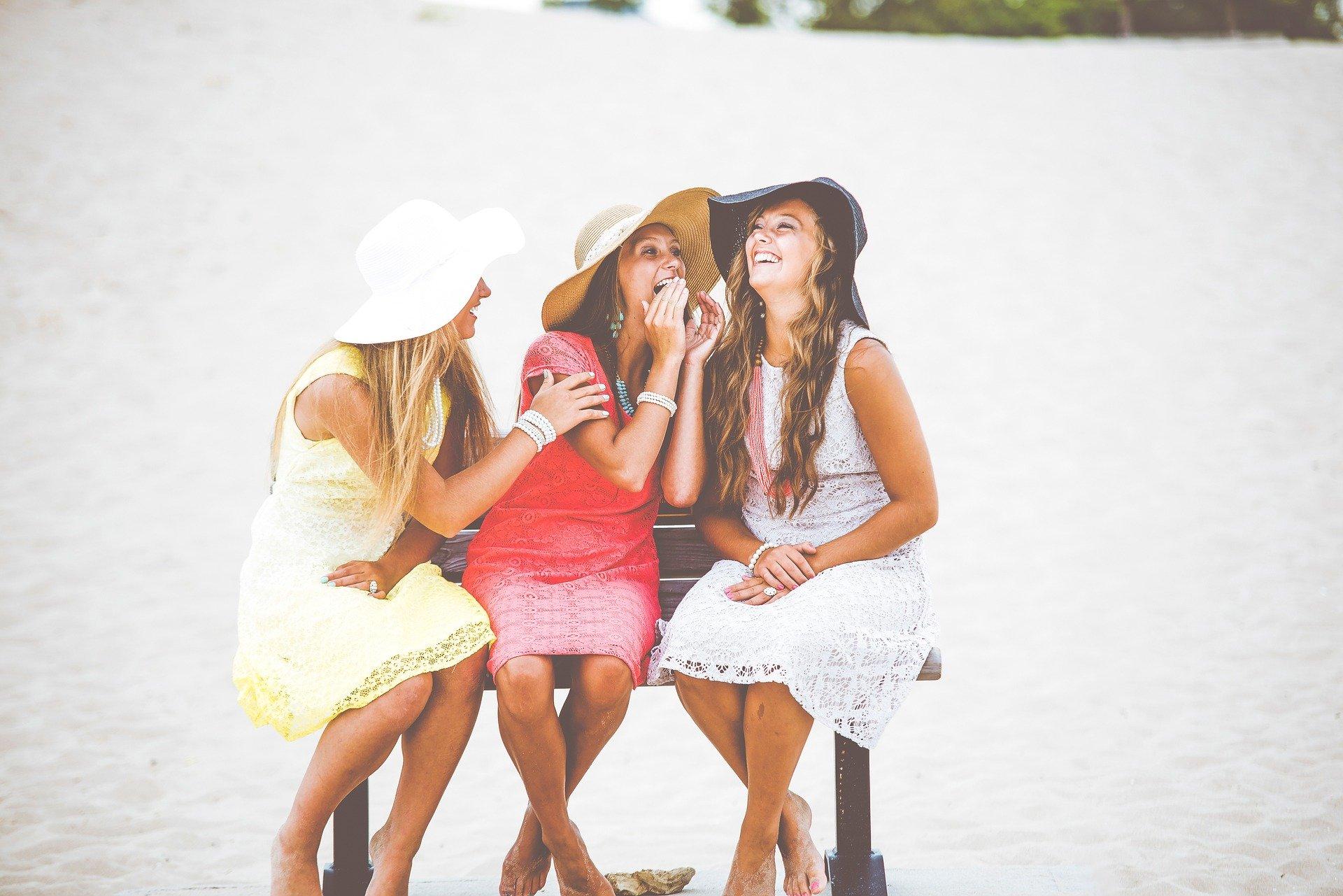 Trzy roześmiane kobiety w kapeluszach i kolorowych sukienkach, siedzące razem na ławce na brzegu jeziora