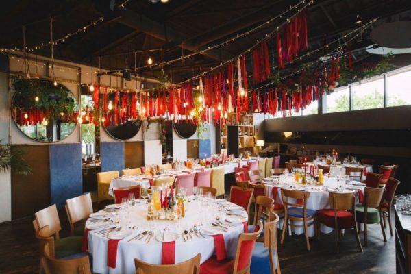 Wnętrze restauracji weselnej z podwieszonymi dekoracjami świetlnymi oraz kolorowymi wstążkami