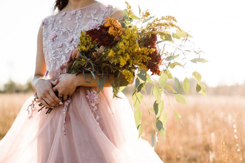 Panna Młoda na polu, w pudrowej, koronkowej sukni trzymająca bukiet z polnymi kwiatami