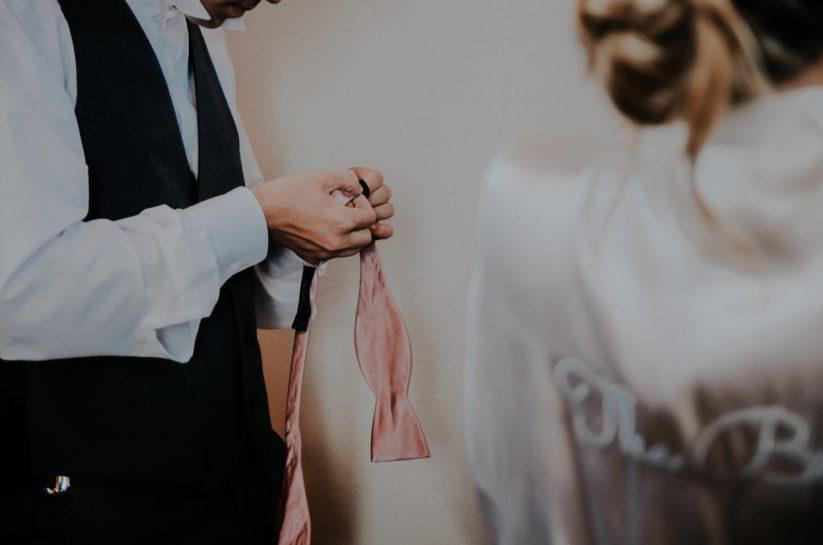 Pan Młody ubierający różową, wiązaną muszę, w tle Panna Młoda w satynowym szlafroku