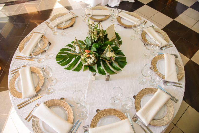 Elegancki, okrągły stół weselny z białym obrusem, złotymi podtalerzami i dużą zieloną dekoracją kwiatową