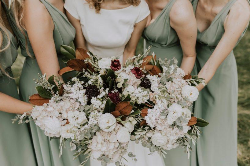 Panna Młoda z druhnami w miętowych sukniach trzymające swoje wiązanki ślubne i tworzące z nich jeden, duży, kolorowy bukiet