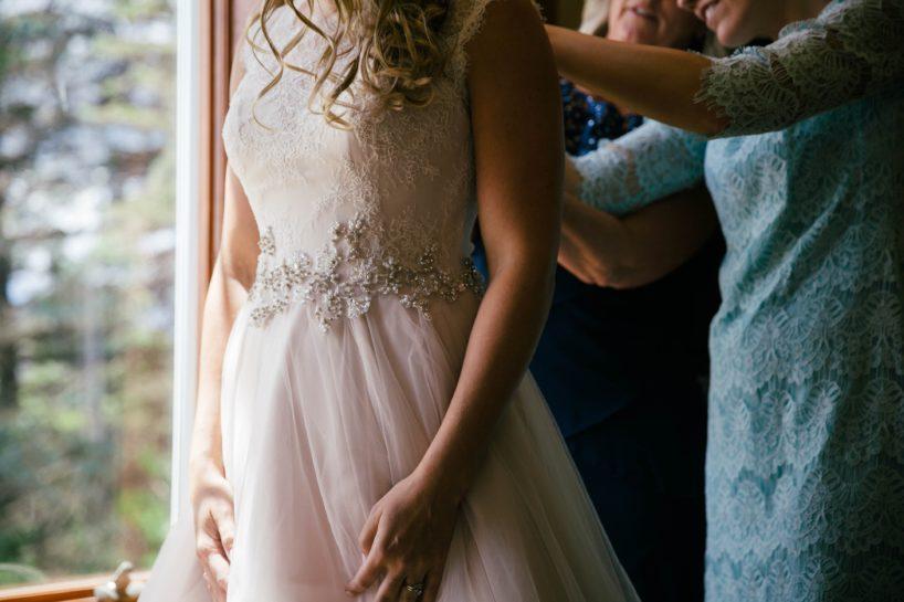 Panna Młoda w koronkowej, pudrowej sukni ślubnej, w tle dwie Panie zapinające i poprawiające suknię