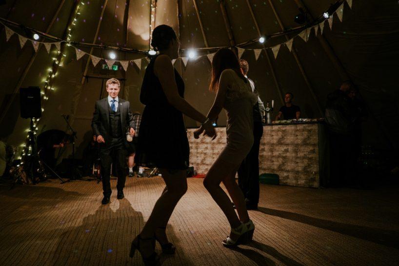 Goście bawiący się w świetle lampek i kolorowych reflektorów na weselu.