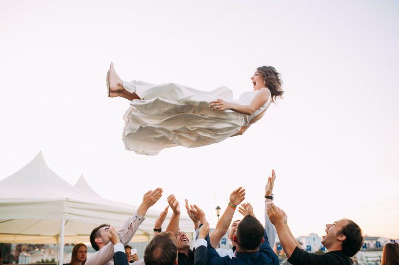 Podrzucona przez gości weselnych roześmiana Panna Młoda w białej sukni ślubnej.