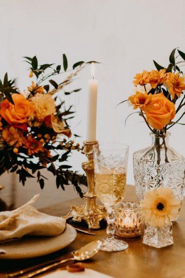 Karafki z pomarańczowymi kwiatami, złoty świecznik i kryształowy kieliszek, What a lovely day Wedding Planner