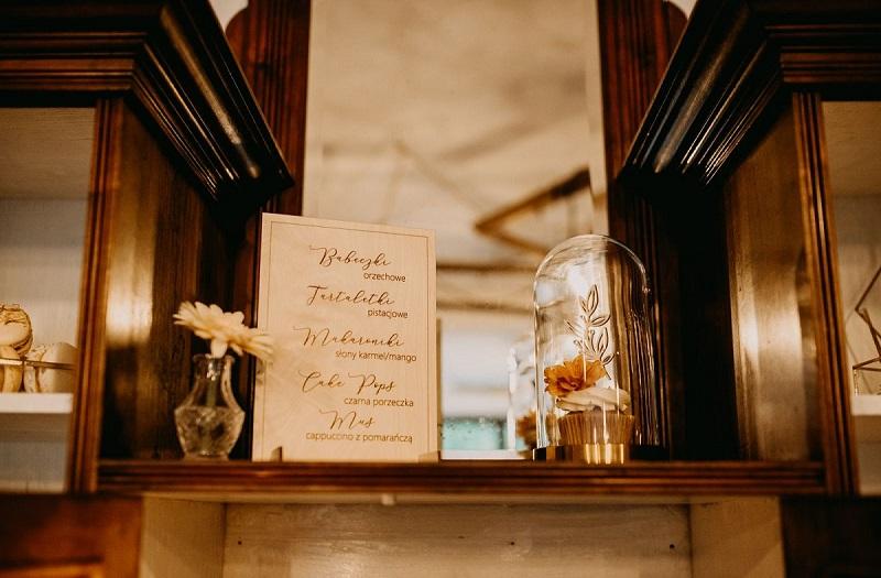Drewniany kredens, tabliczka z wypisanymi słodkościami, słodka babeczka pod ozdobnym kloszem, What a lovely day Wedding Planner