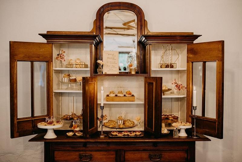 Drewniany kredens wypełniony słodyczami, świece, karafki z kwiatami, What a lovely day Wedding Planner