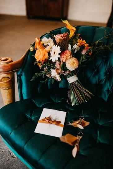 Fotel w kolorze butelkowej zieleni, a na nim bukiet ślubny, zaproszenie i kolczyki, What a lovely day Wedding Planner