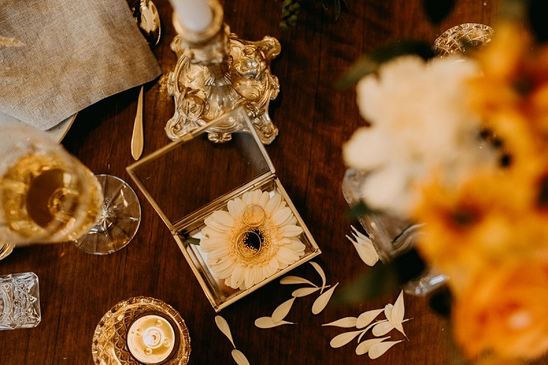 Flat lay z ozdobną szkatułką, a w niej ułożone na płatkach kwiatów obrączki, What a lovely day Wedding Planner