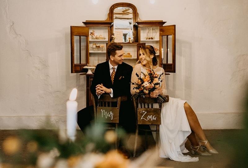 Siedząca, zapatrzona w siebie Para Młoda, w tle kredens ze słodkościami, What a lovely day Wedding Planner