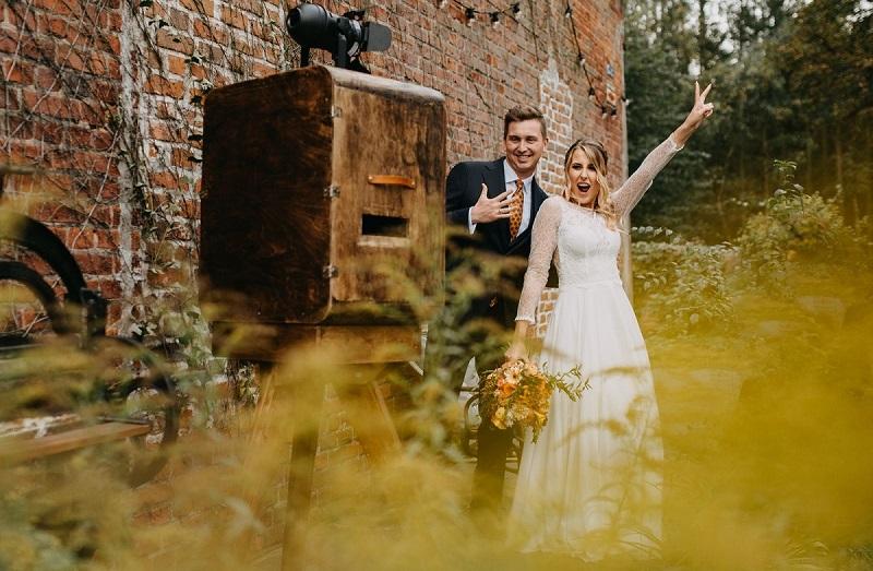 Pozująca przy drewnianej fotobudce roześmiana Para Młoda, What a lovely day Wedding Planner
