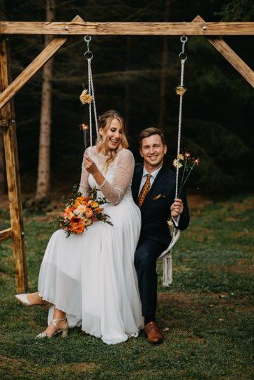 Uśmiechnięta Para Młoda na huśtawce, w rękach trzymają zimne ognie, What a lovely day Wedding Planner