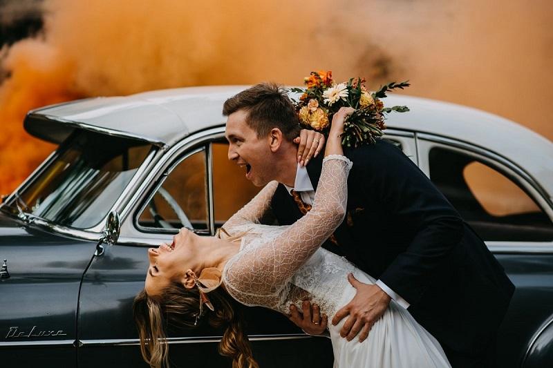 Para Młoda w swoich objęciach, w tle pomarańczowy dym i zabytkowy samochód, What a lovely day Wedding Planner