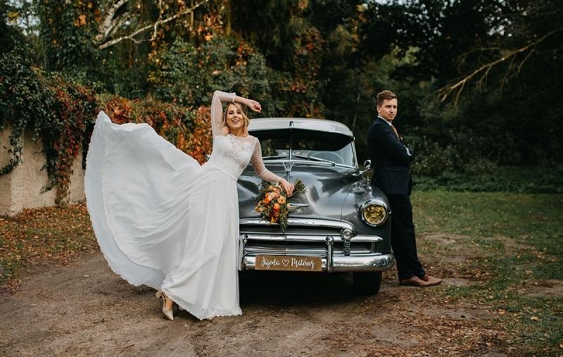 Oparta o zabytkowy samochód Para Młoda, Pani Młoda w rozwianej, białej sukni, What a lovely day Wedding Planner