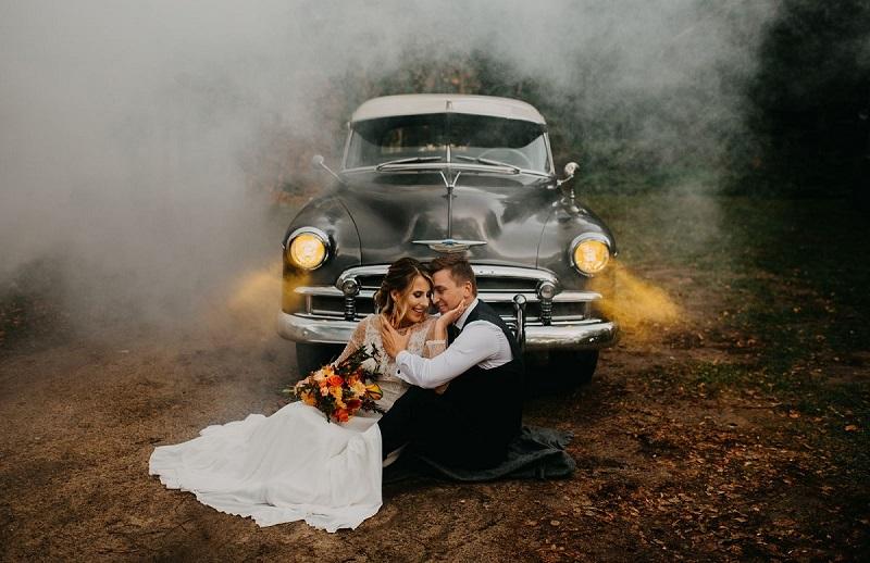 Siedząca na kocu przed zabytkowym samochodem Para Młoda, w tle biały dym i światło reflektorów, What a lovely day Wedding Planner