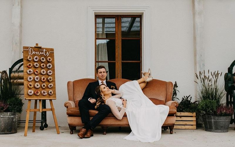 Para Młoda siedząca na kolorowej kanapie, Panna Młoda opiera głowę na kolanach Pana Młodego, obok tablica z kolorowymi pączkami, What a lovely day Wedding Planner