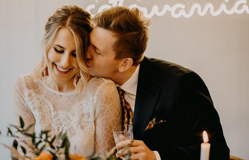 Portret uśmiechniętej Pary Młodej, Pan Młody daje swojej żonie buziaka w policzek, What a lovely day Wedding Planner