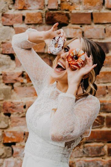 Roześmiana Panna Młoda przykładająca kolorowe pączki do swojej twarzy, What a lovely day Wedding Planner