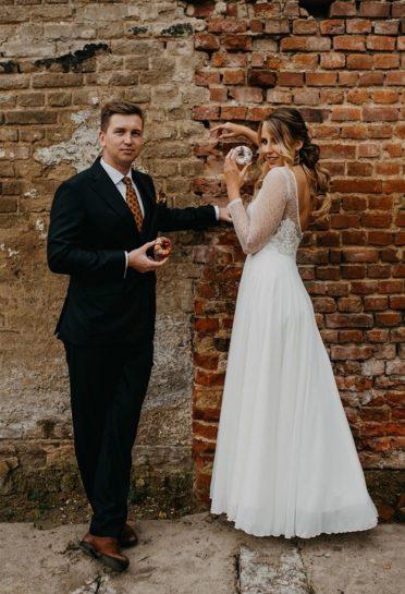 Para Młoda na tle ceglanej ściany, trzymająca kolorowe donuty, What a lovely day Wedding Planner