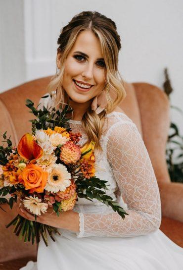 Porter uśmiechniętej Panny Młodej trzymającej kolorowy, jesienny bukiet kwiatów, What a lovely day Wedding Planner