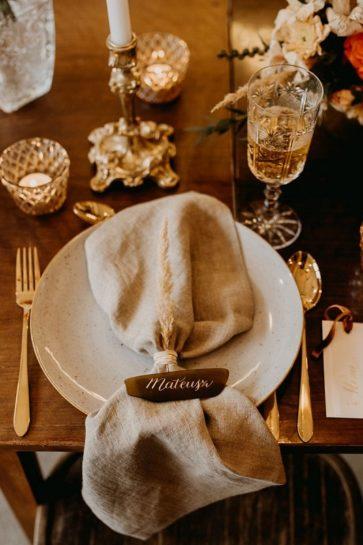 Zastawa ślubna- złote sztućce, beżowy talerz, na nim lniana serwetka z brązową, kaligrafowaną winietką, What a lovely day Wedding Planner