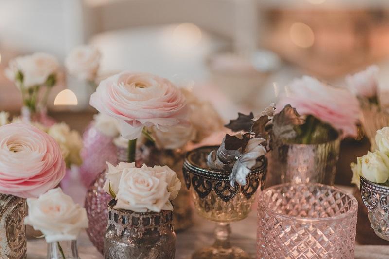 Szklane wazoniki i pudrowe oraz kremowe kwiaty na stole ślubnym, What a lovely day Wedding Planner