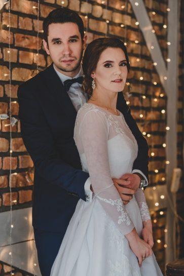 Portret Pary Młodej na tle ściany z surowych cegieł i lampek, What a lovely day Wedding Planner