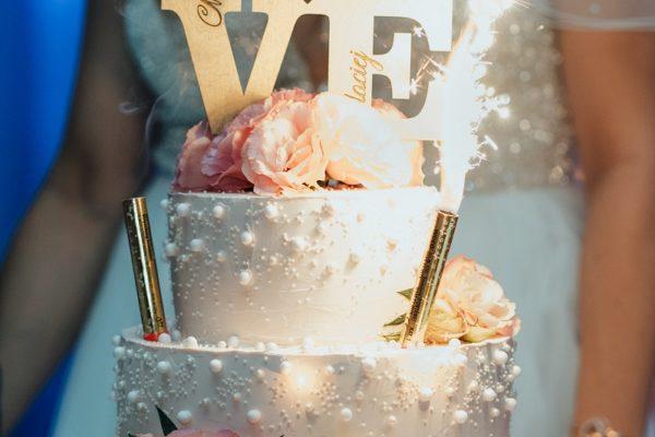 Piętrowy tort ślubny z perełkami i płatkami kwiatów oraz drewnianym topperem