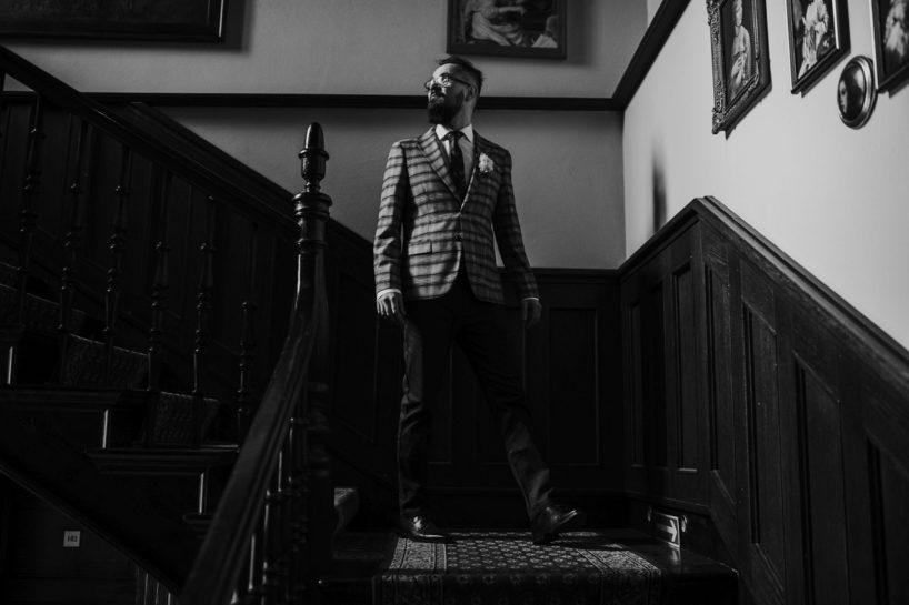 Czarno białe zdjęcie Pana Młodego schodzącego po schodach w Pałacu Śródka, What a lovely day Wedding Planner Poznań