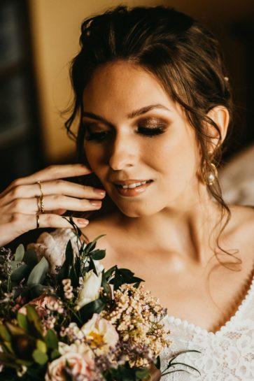 Portret Panny Młodej w mocnym makijażu, eksponująca ozdobne pierścionki na dłoni, What a lovely day Wedding Planner Poznań