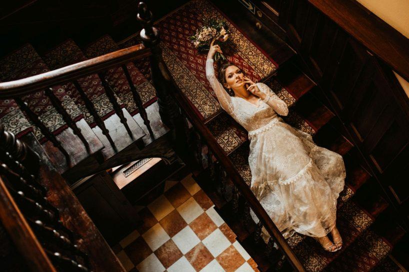 Portret Panny Młodej leżącej na zabytkowych schodach Pałacu Śródka, What a lovely day Wedding Planner Poznań
