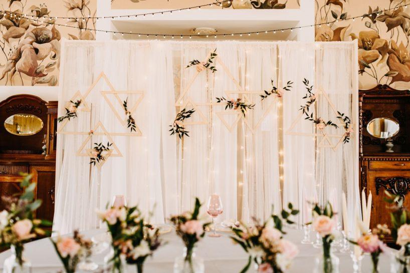 Tiulowa ścianka oświetlona lampkami i udekorowana geometrycznymi, drewnianymi dekoracjami, What a lovely day Wedding Planner Poznań
